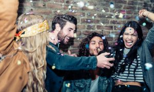 Friends making big party in the night. Four people throwing confetti and drinking champagne